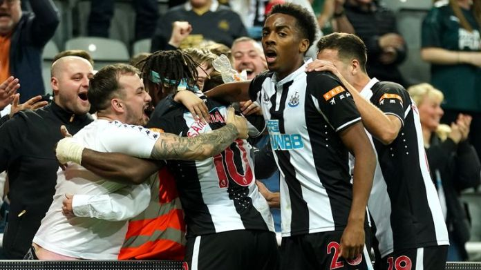 Newcastle United's Allan Saint-Maximin (hidden) celebrates scoring their side's first goal of the game with team-mates and fans during the Premier League match at St James' Park, Newcastle. Picture date: Friday September 17, 2021.