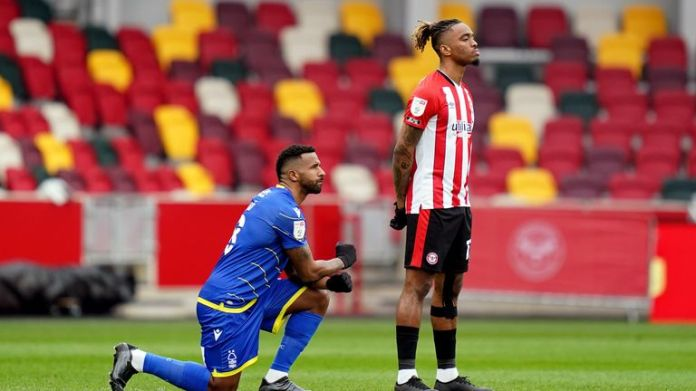 Ivan Toney stands as a rival player takes the knee