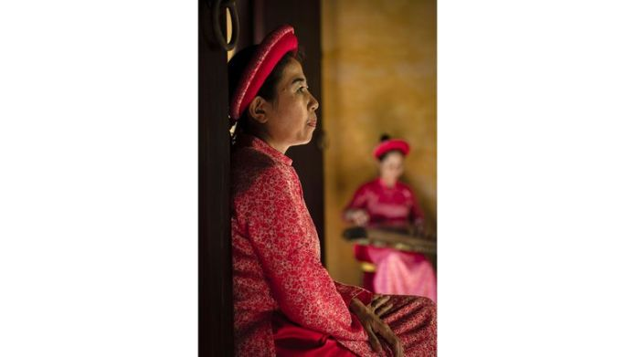 Undated handout photo issued by the National Geographic of Vietnamese woman in traditional clothing sitting in the Hue Imperial City's palace. The image, taken by Walter Monticelli, was the runner-up in the people category at the National Geographic Traveller (UK) Photography Competition 2021. Issue date: Tuesday October 5, 2021.