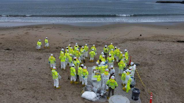 Workers rake up globs of crude oil on Newport Beach