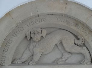 """At the entrance, a dog stone figure can be found, as a symbol of fidelity. The words say """"Faithfulness keeps watch by day and night"""""""