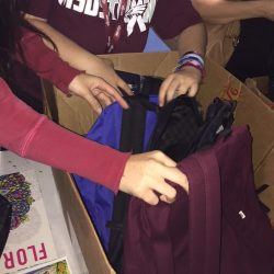 Junior Shai Harnov picks out her free Vans backpack. Photo by Lauren Newman