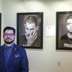 "Standing with Pride. Photojournalist Ian Witlen stands in front of his ""Anguish in the Aftermath"" exhibit at the Coral Springs Center for the Performing Arts on Sept. 26, moments before the opening ceremony begins. Photo courtesy of Chris Zuppa"