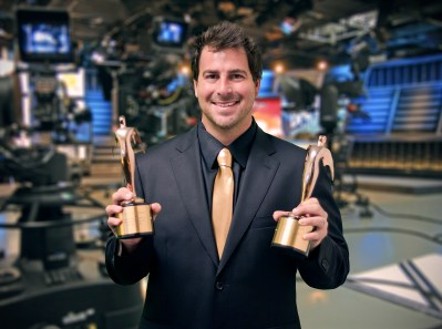 """Evan Golden displays two of his awards on the set of  """"Eye on South Florida"""" . Photo Courtesy of Jack Namer"""
