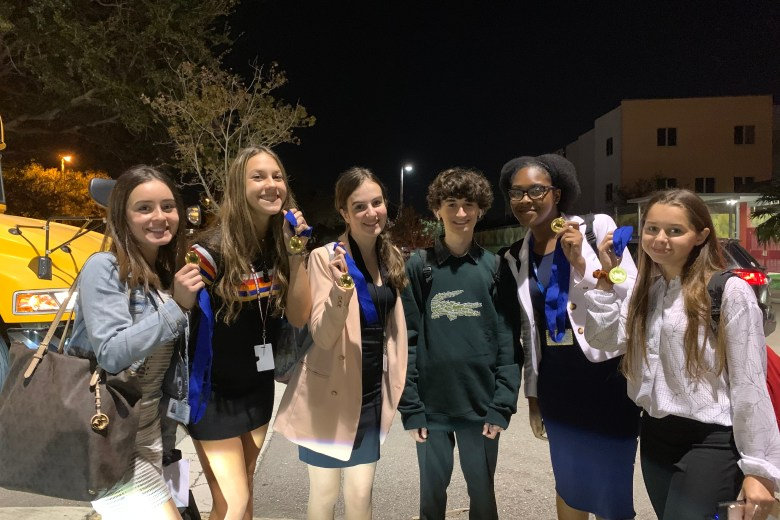MSD's speech and debate students hold up medals earned from their last tournament of the first semester.