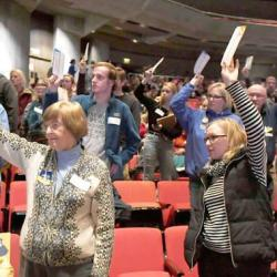 Iowa Caucus goers raise their hands. Caucus-goers raise their hands to be counted during the caucuses at Stephen Auditorium Monday, Feb. 3, 2020, in Ames, Iowa. Photo by Nirmalendu Majumdar/Ames Tribune