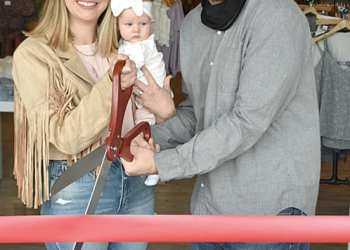 Alison, Tommy and four-month-old McKenna Ryan cut the ribbon on Apricot Lane Boutique on Friday, May 7. The Ryans have reopened the store, which closed last November under previous ownership. (Photo: David Tyler)