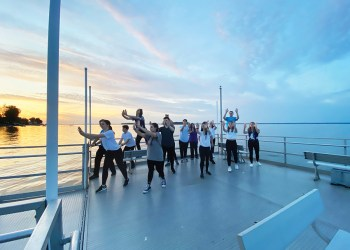 A group of students dances on a dock at sunset