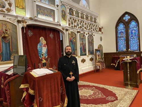 Father Kyrillos Sadek stands in the sanctuary of St. Mary and St. Mina Coptic Church in North Syracuse. He is a Coptic priest wearing black vestments.