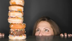 woman looking at stack of donuts