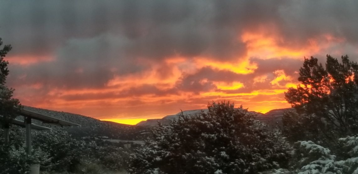 The sun brightens dark clouds, rising over snow-covered trees and hills