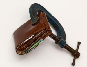 A vise clamping a wallet