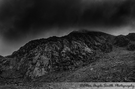 Tryfan's North ridge towers over the road, as a false summit disappears into the clag. A very popular climbing venue, Milestone Buttress is on the lower left and has climbers on it, but you may find them hard to make out.