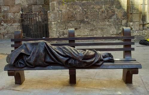 Estàtua de bronze d'una persona sensesostre dormint en un banc