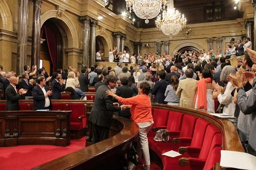 El President Carles Puigdemont dona la mà a la consellera de Treball, Afers Socials i Famílies, Montse Bassa, a la bancada del Parlament de Catalunya.