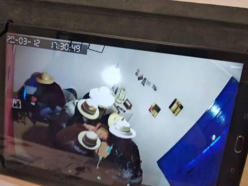 Imatge de 5 participants a l'escape room amb uns barrets posats, asseguts en una taula parlant.