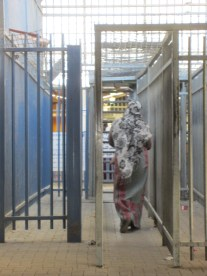 A woman walks through Qalandiya checkpoint. Instead of direct access to East Jerusalem, Ar Ram citizens must go through the wire cages of the checkpoint. Photo EAPPI.