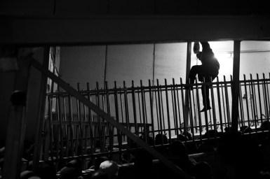 06.01.16. CP300. Man climbs bars of CP300 to avoid queue. Photo EAPPI/P. Morgan