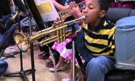 armless boy plays trumpet