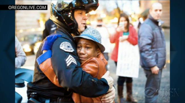 "12 Year Old Protesting In Oregon Holds Sign That Says, "" Free Hugs"" An Officer Obliged By Giving Him A Hug"