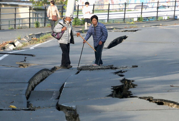 Local residents look at cracks caused by an earthquake on a road in Mashiki town, Kumamoto prefecture, southern Japan, in this photo taken by Kyodo April 16, 2016. Mandatory credit REUTERS/Kyodo ATTENTION EDITORS - FOR EDITORIAL USE ONLY. NOT FOR SALE FOR MARKETING OR ADVERTISING CAMPAIGNS. MANDATORY CREDIT. JAPAN OUT. NO COMMERCIAL OR EDITORIAL SALES IN JAPAN. THIS IMAGE WAS PROCESSED BY REUTERS TO ENHANCE QUALITY, AN UNPROCESSED VERSION WILL BE PROVIDED SEPARATELY.