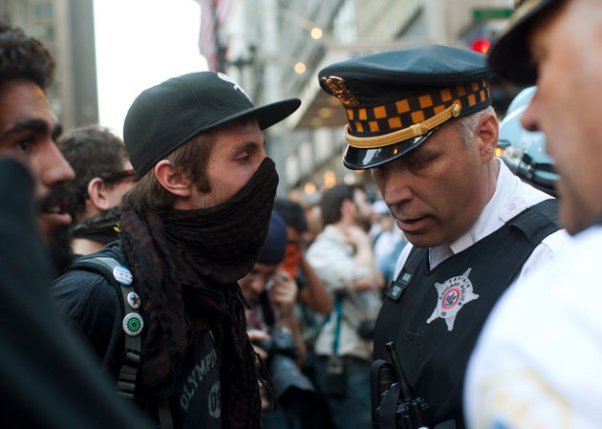 A protester faces off with a Chicago police officer during an anti-NATO protest march in Chicago May 19, 2012. Hundreds of demonstrators protested peacefully on Saturday on the eve of the NATO summit in Chicago, gathering outside Mayor Rahm Emanuel's home to criticize cuts in mental health services before moving downtown under the close eye of police. REUTERS/Andrew Kelly (UNITED STATES - Tags: POLITICS MILITARY CIVIL UNREST)