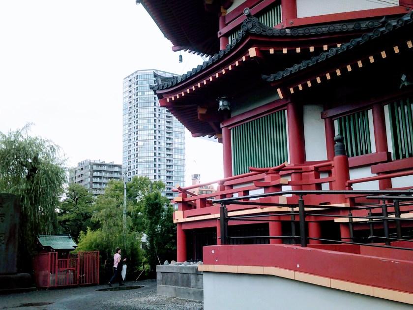Red Buddhist Temple alongside modern skyscraper in Tokyo