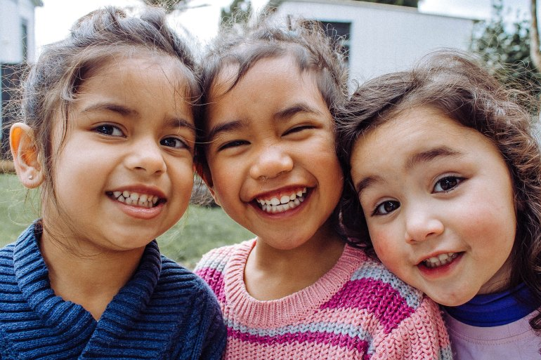 A group of three children smiling broadly