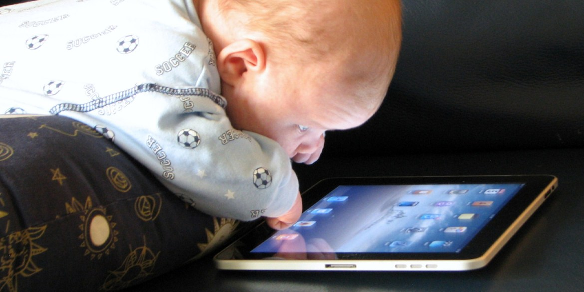 A baby peering closely at an iPad