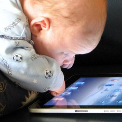 A baby peering closely at an iPad
