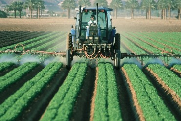 A tractor spraying a large farm field