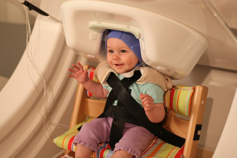 A baby smiles while being tested by a Magnetoencephalography (MEG) machine
