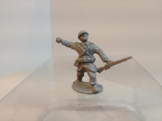 Infantryman throwing grenade, carring rifle wearing coat, webbin
