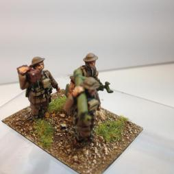Stokes mortar team of 3 men carrying mortar in sections forward.