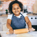 child smiling baking rolling using a rolling pin cooking EYFS