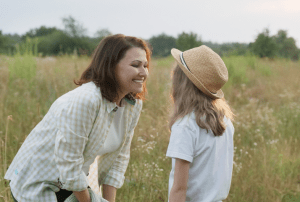 ,other mum talking to daughter girl in a field. communication within the early years foundation stage