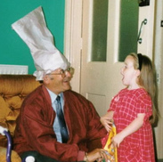 grandpa with chef hat laughing with granddaughter