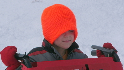 boy smiling while using snowblower
