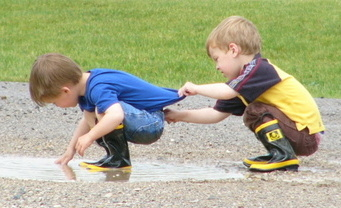 toddler shoving mud into brother's pants