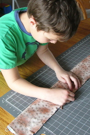 boy putting pins in fabric