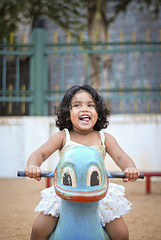 girl joyfully playing on playground toy