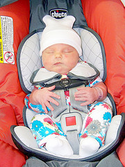 small baby strapped into carseat
