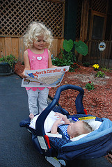 small girl reading map to baby