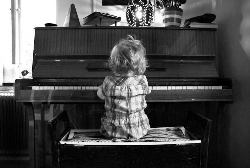back of toddler girl sitting at piano