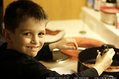 boy at stove cooking while smiling at camera