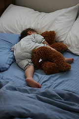 boy asleep snuggling with stuffed bear