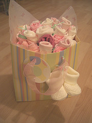 gift bag of pink baby clothes folded to look like roses