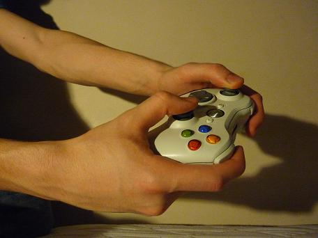 pair of hands holding video game controller