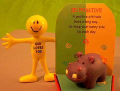 plastic toy saying God loves you, card saying Be Positive