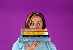 woman with stack of books in front of face